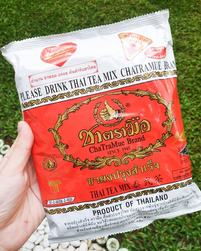 A hand holding a pack of Cha Tra Mue Thai tea mix